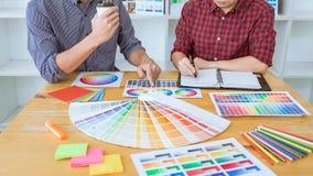 Laget av det idérika grafiska märkes- mötet som arbetar på nytt projekt, väljer valfärg och att dra på diagramminnestavlan med ar fotografering för bildbyråer