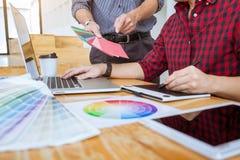 Laget av det idérika grafiska märkes- mötet som arbetar på nytt projekt, väljer valfärg och att dra på diagramminnestavlan med ar royaltyfria bilder