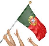 Laget av folk räcker att lyfta den Portugal nationsflaggan Arkivfoton