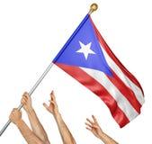 Laget av folk räcker att lyfta den Puerto Rico nationsflaggan Arkivfoton