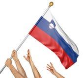 Laget av folk räcker att lyfta den Slovenien nationsflaggan Arkivfoton