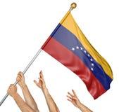 Laget av folk räcker att lyfta den Venezuela nationsflaggan Arkivbilder