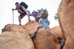 Laget av klättrare man och kvinna hjälper sig överst av mountaen arkivbilder