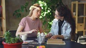 Laget av två idérika formgivare ser bilder och talar om dem, medan sitta tillsammans på skrivbordet Skott på Canon 5D fläck II me stock video