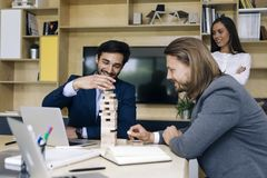 Laget av ungt affärsfolk bygger en träkonstruktion royaltyfria bilder