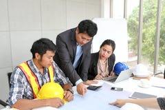 Laget iscensätter funktionsduglig mötesrum på kontoret Lagarbetare talar konstruktionsplan Elektrikersnickare eller tekniskt Royaltyfria Foton