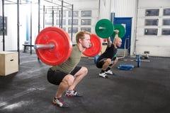 Laget utbildar squats på konditionidrottshallmitten Royaltyfri Bild