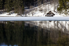Laghi di Fusine. A little house covered by snow reflected upon the lake's water Winter location royalty free stock image