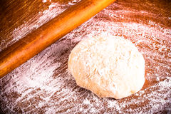 Laghman dough on an old wooden worn board with flour. Toned Stock Images