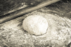 Laghman dough on an old wooden worn board with flour. Toned Stock Photography