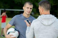 Lagledare med stoppuren som talar till den unga manliga spelaren royaltyfri foto