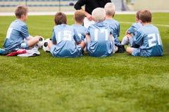 Lagledare som ger unga anvisningar för fotbolllag Ungdomfotboll Team With Coach royaltyfria foton
