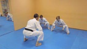 Lagledaren Aikido fungerar med barn i idrottshallen arkivfilmer