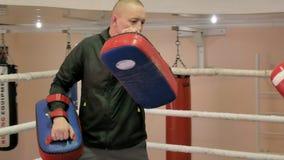 Lagledaren för en utbildningsstrid med tafsar med en kvinnlig kickboxer i cirkeln royaltyfria foton