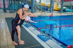Lagledaren i vattnet parkerar undervisar lite flickan att simma arkivfoto