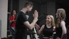 Lagledaren kommer till att hälsa till bra flickor i ny idrottshall och höjdpunkt fem och frågar om dem med flickan som är förlova stock video