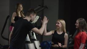 Lagledaren kommer till att hälsa till trevliga flickor i ny idrottshall och höjdpunkt fem och frågar om dem med flickan som är fö stock video