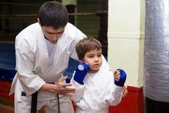 Lagledaren utbildar unga tonåringar i karategrupp royaltyfria foton