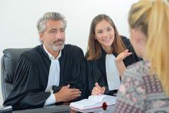 Lagliga arbetare i ämbetsdräkter som talar till klienten Arkivbilder