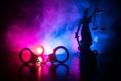 Lagligt lagbegrepp Konturn av handbojor med statyn av rättvisa på bak med den blinkande röda och blåa polisen tänder på royaltyfria foton