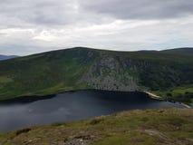 Lago acurrucado en valle de la montaña Fotografía de archivo