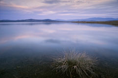 Lago ad anche dopo il tramonto con esposizione lunga fotografia stock
