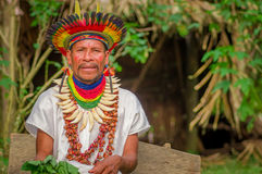 LAGO AGRIO, ECUADOR - NOVEMBER 17, 2016: Siona shaman in traditional dress with a feather hat in an indigenous village. In the Cuyabeno Wildlife Reserve Royalty Free Stock Photos