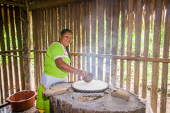 LAGO AGRIO, ECUADOR - NOVEMBER, 17 2016: Woman demonstrates cooking yucca tortillas in an indoors kitchen in a Siona Stock Image