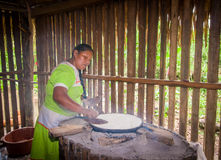 LAGO AGRIO, ECUADOR - NOVEMBER, 17 2016: Woman demonstrates cooking yucca tortillas in an indoors kitchen in a Siona. Village in the Cuyabeno Wildlife Reserve royalty free stock images