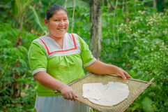 LAGO AGRIO, ECUADOR - NOVEMBER, 17 2016: Woman demonstrates cooking yucca tortillas in an outdoor kitchen in a Siona. Village in the Cuyabeno Wildlife Reserve stock photo