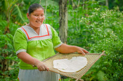 LAGO AGRIO, ECUADOR - NOVEMBER, 17 2016: Woman demonstrates cooking yucca tortillas in an outdoor kitchen in a Siona. Village in the Cuyabeno Wildlife Reserve royalty free stock photography