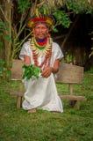 LAGO AGRIO, EQUADOR - 17 DE NOVEMBRO DE 2016: Curandeiro de Siona no vestido tradicional com um chapéu da pena em uma vila nativa imagens de stock royalty free