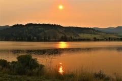 Lago alaranjado dourado do espelho do nascer do sol da montanha de Montana foto de stock