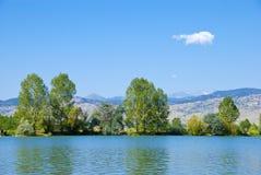 Lago, alberi, montagne e nube Wispy immagini stock