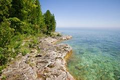 Lago alla destra, terreno roccioso con gli alberi a sinistra nel parco di stato della penisola nella contea di Door Wisconsin fotografie stock libere da diritti