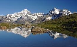 Lago alpino con la reflexión de montañas en agua imágenes de archivo libres de regalías