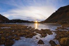 Lago alpino congelato elevata altitudine, riflessioni al tramonto Fotografie Stock Libere da Diritti