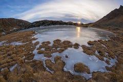 Lago alpino congelato elevata altitudine, vista del fisheye al tramonto Immagine Stock Libera da Diritti