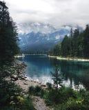 Lago alpino Eibsee con chiara acqua blu, circondata dagli alberi e dalle montagne coperti di nebbia, colpo verticale, Baviera fotografia stock libera da diritti