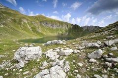 Lago alpino el día soleado Imagen de archivo libre de regalías