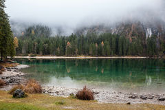 Lago alpino nella mattina nebbiosa Immagine Stock