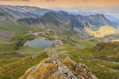 Lago alpino y camino curvado en montañas, Transfagarasan, montañas de Fagaras, Cárpatos, Rumania fotografía de archivo