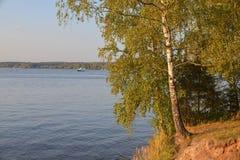 Lago amarilleado contra un lago con un yate imagen de archivo