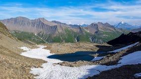 Lago azul cercado pela neve nos cumes europeus Excursão De Mont Blanc, França fotografia de stock royalty free