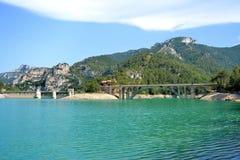 Lago azul claro com ponte e montanhas Imagem de Stock