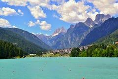 Lago azul con los carriles debajo de un cielo azul con las nubes blancas en montañas Fotos de archivo libres de regalías