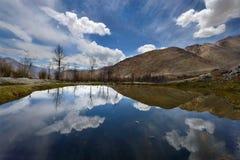 Lago azul entre as montanhas altas: as inclinações dos montes, das nuvens brancas e do céu azul são refletidas na superfície da á Imagem de Stock