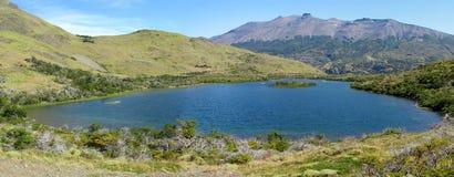 Lago blu circondato dalle colline verdi Fotografia Stock Libera da Diritti