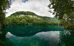 Lago blu della montagna con la barca blu e rossa un giorno nuvoloso Fotografia Stock Libera da Diritti