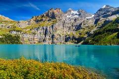 Lago blu sbalorditivo con le alte montagne ed i ghiacciai, Oeschinensee, Svizzera Immagini Stock